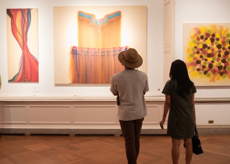 Two patrons admiring work from Full Circle: Hue and Saturation in the Washington Color School