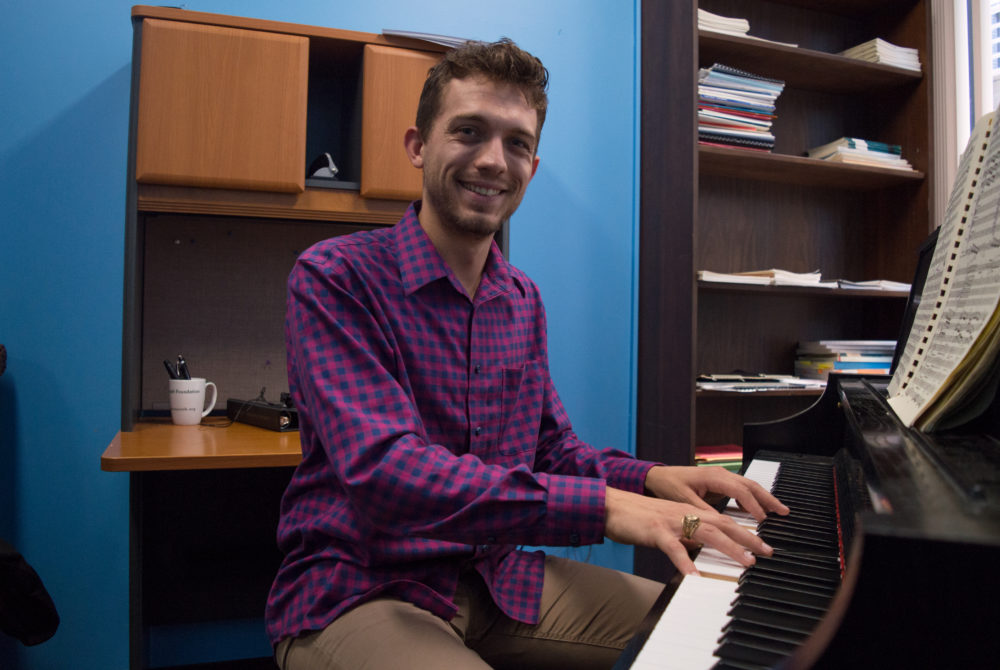 photo of new choir director smiling and playing piano