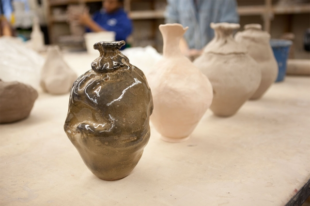 A row of ceramic pots in various stages of completion.