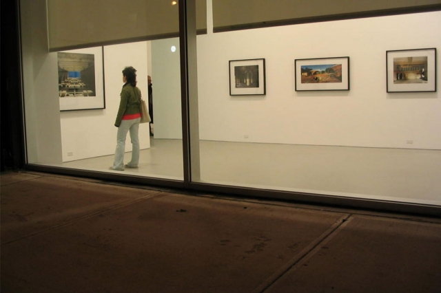 A student, viewed through a window, stands in a gallery