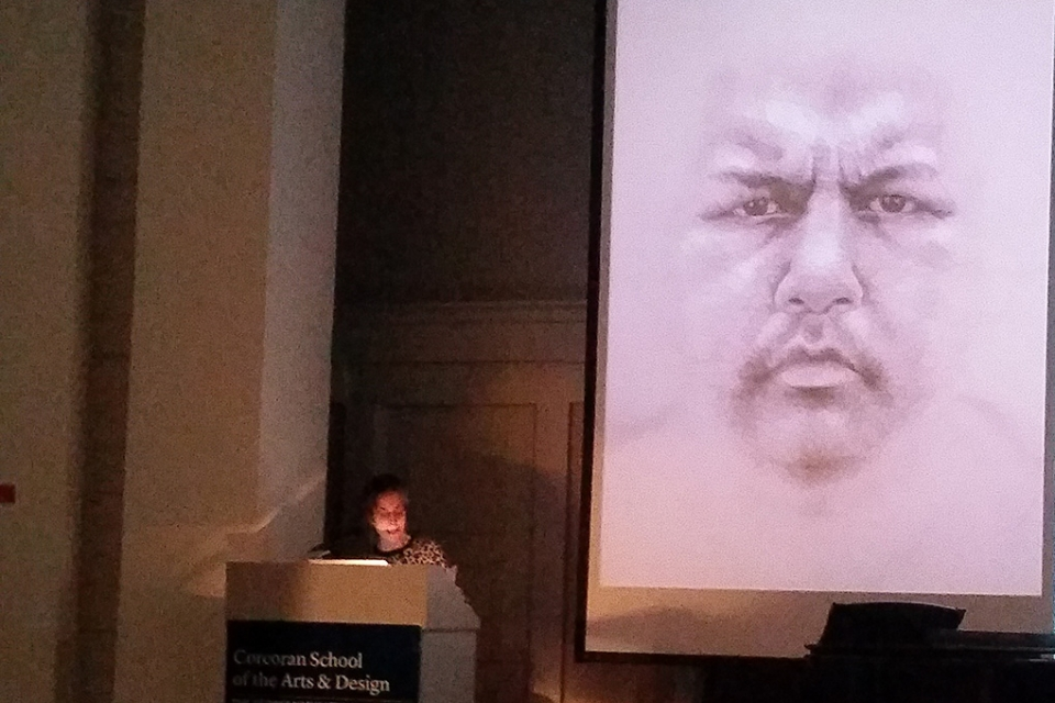 Lynn Sures speaks about an aboriginal face drawing next to her