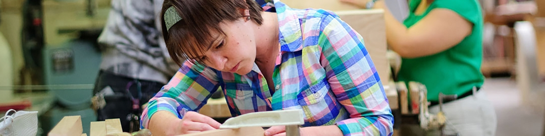 Student concentrating on woodworking tools