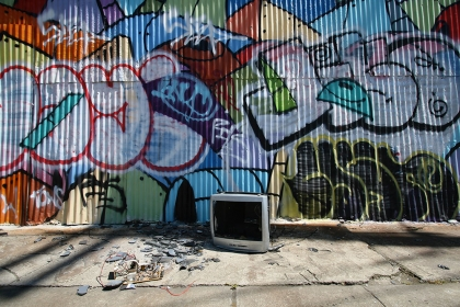 Graffiti adorns a wall behind an abandoned TV