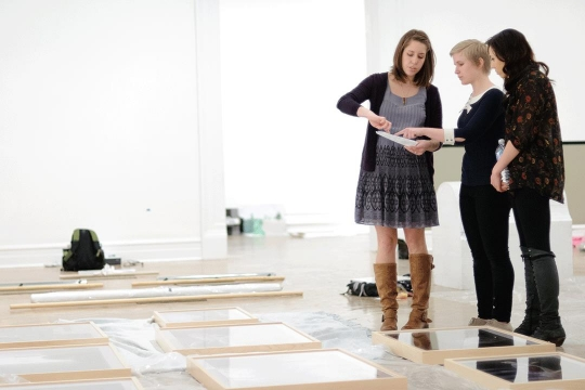 Photo of Three Female Graduate Students Planning Exhibition
