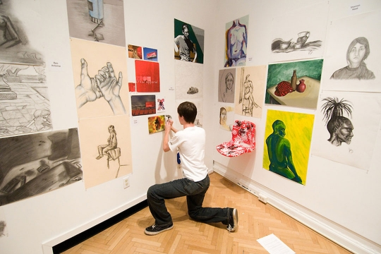 Student kneeling while putting up artwork