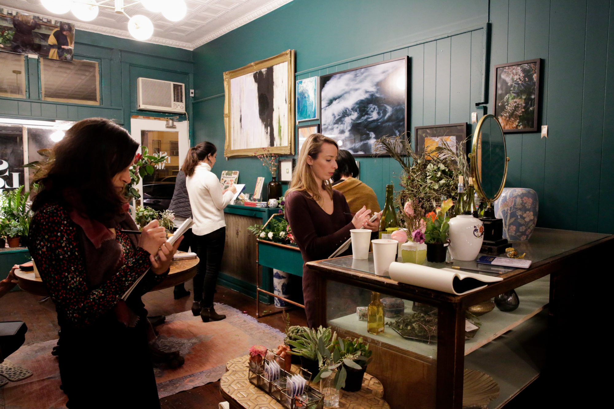 Participants in the Lemon Collective's  Drawing Night work on sketching flowers at She Loves Me, a flower shop that the collective collaborates with frequently.