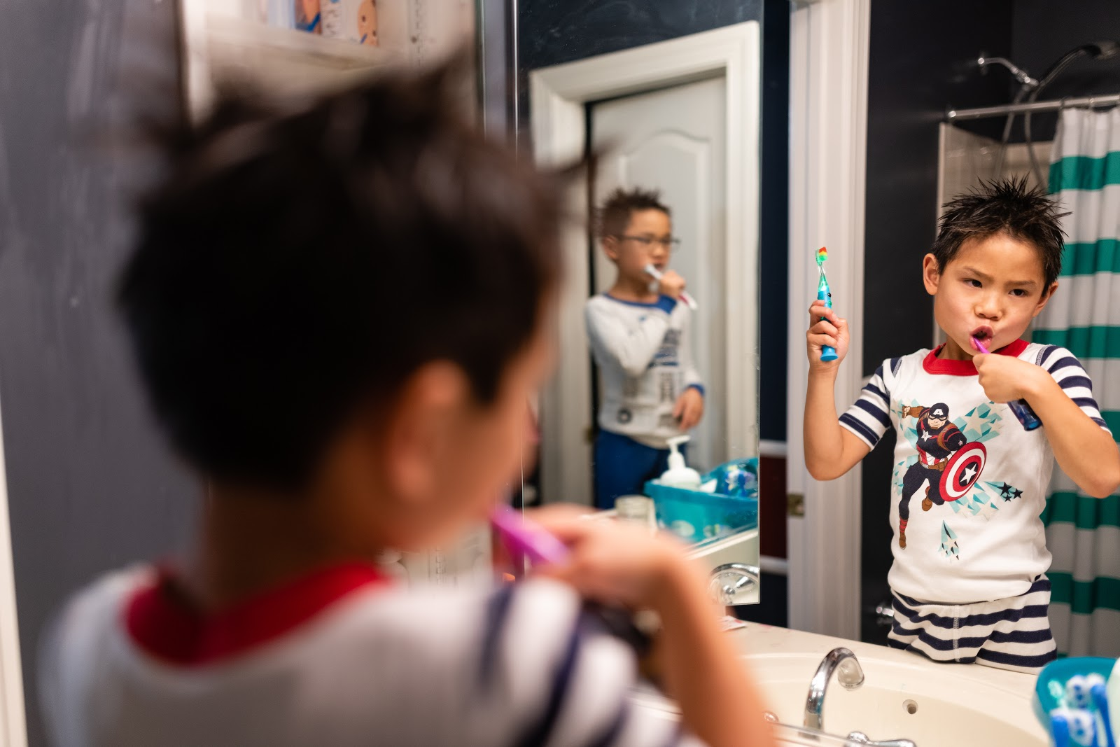 Children brushing teeth in bathroom