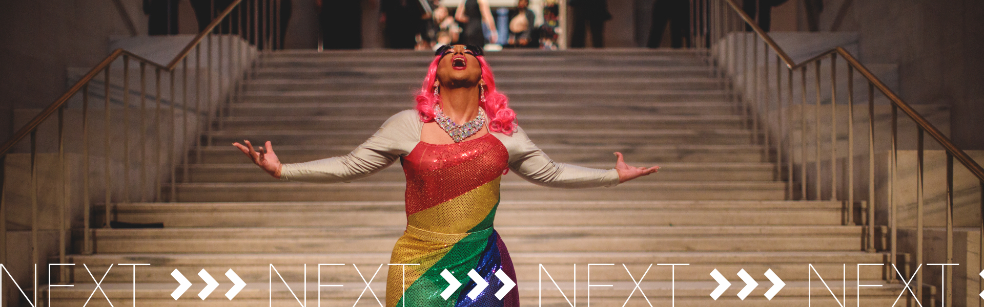 A transgender singer in a colorful rainbow-striped dress holds a note while standing on a staircase