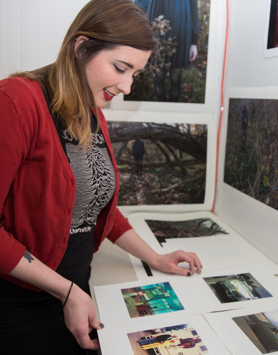Female student looking at display of prints