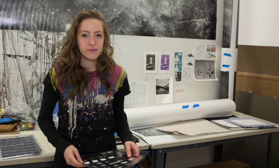 Female student standing in front of her printed work