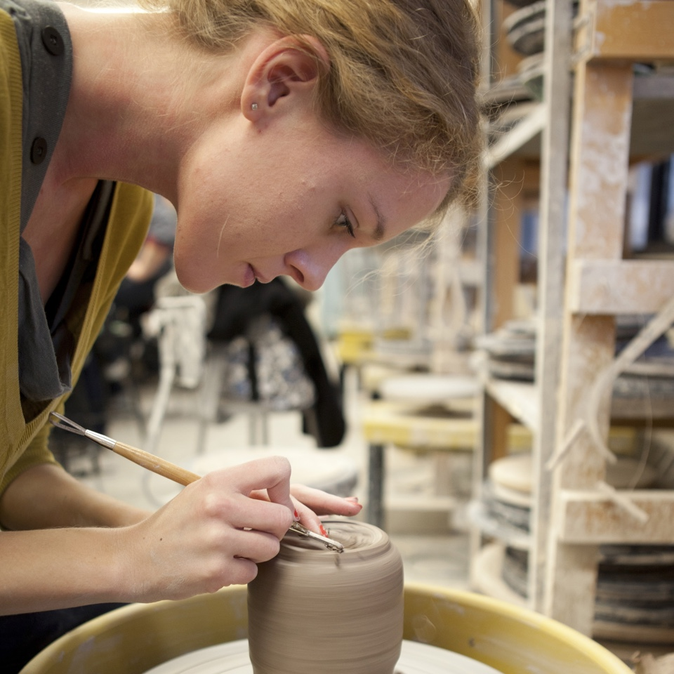 Female student working with clay project on wheel