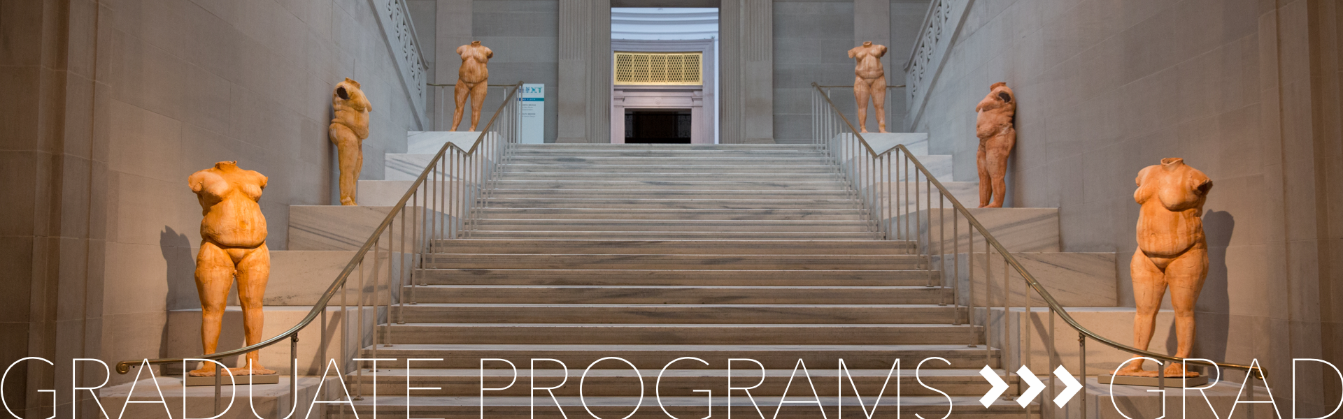Graduate Programs; Statues line the stairs leading to an exhibition space