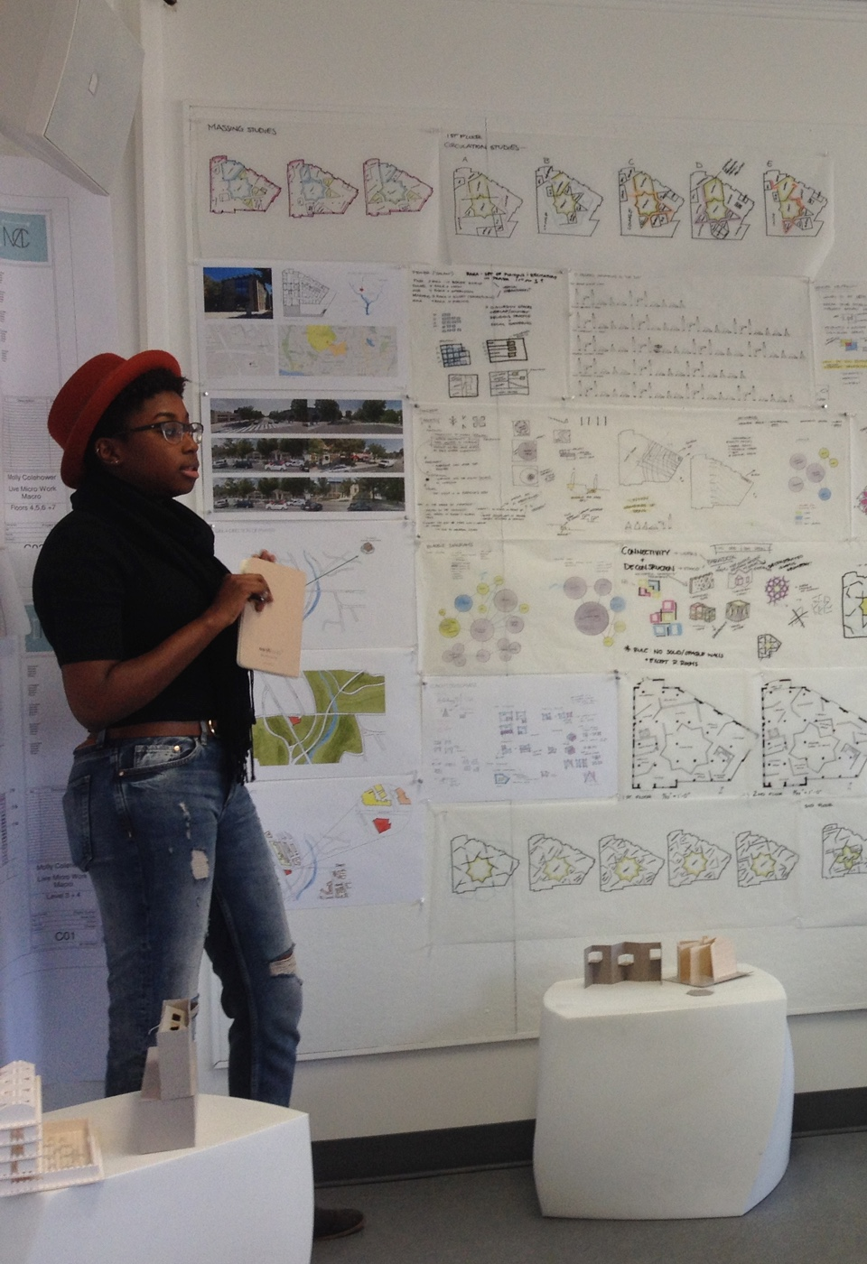 Female student standing with architectural drawings