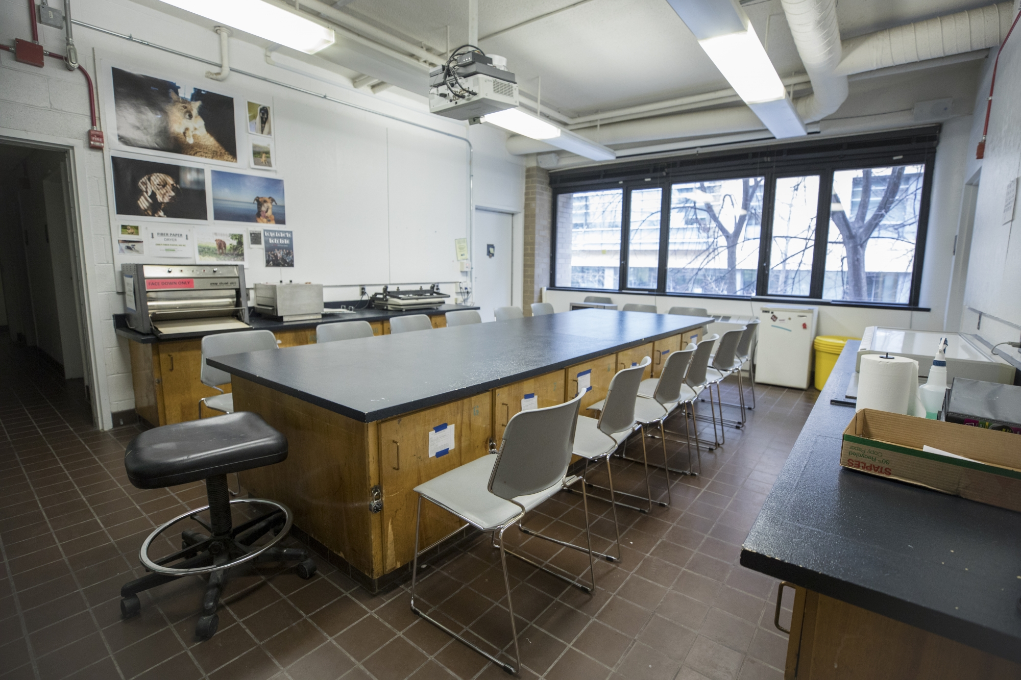 A long lab table with chairs around it in the center of a small classroom