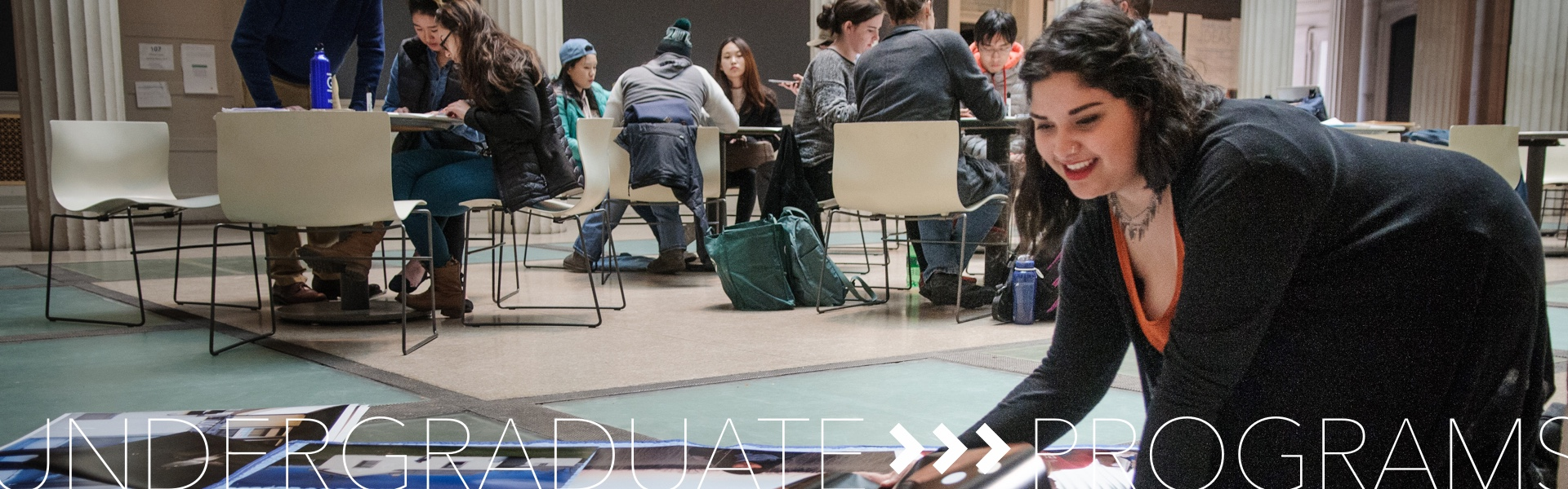 Undergraduate Programs; student working on exhibition in atrium with other students talking at tables in the background