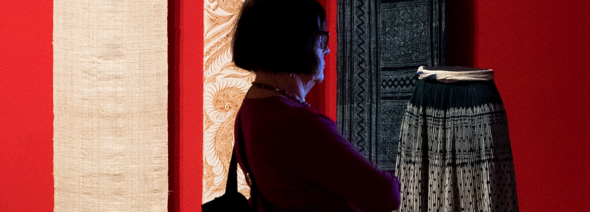 A woman looks at a textile exhibit