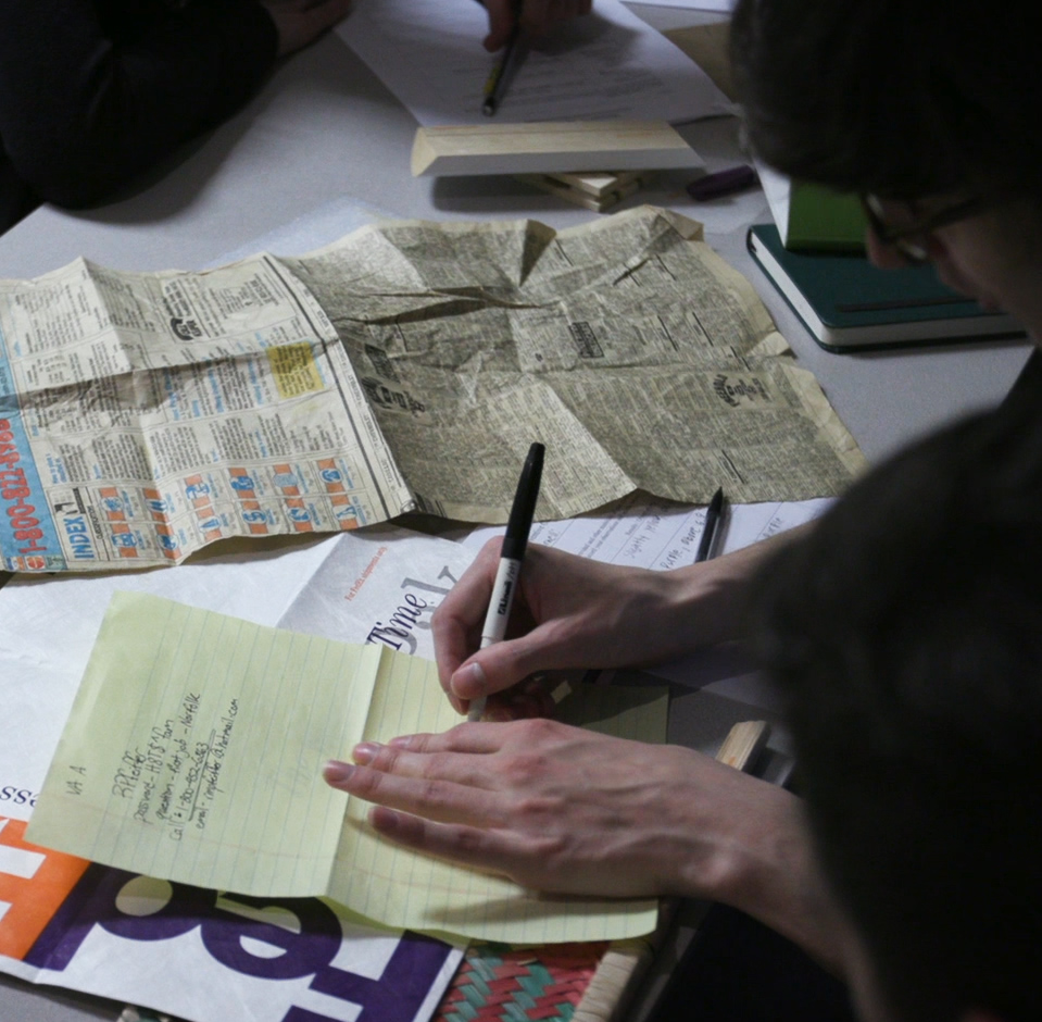 A woman jots down notes while an old newspaper clips sits to her right