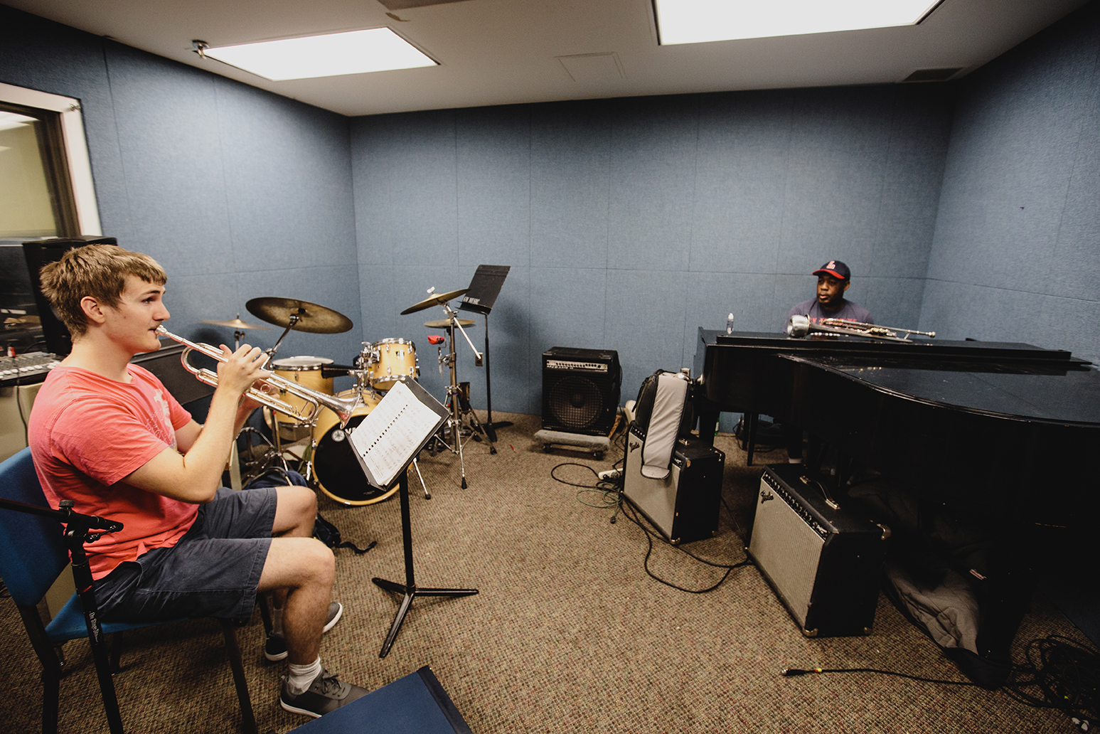 Student plays trombone while instructor supervises