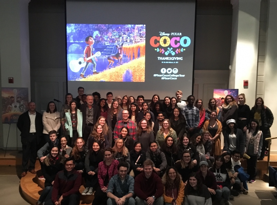 Students posed with Jason Katz in front of screen with movie Coco images