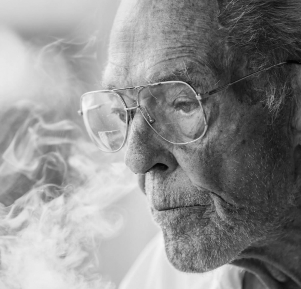 Portrait of an old woman with glasses smoking