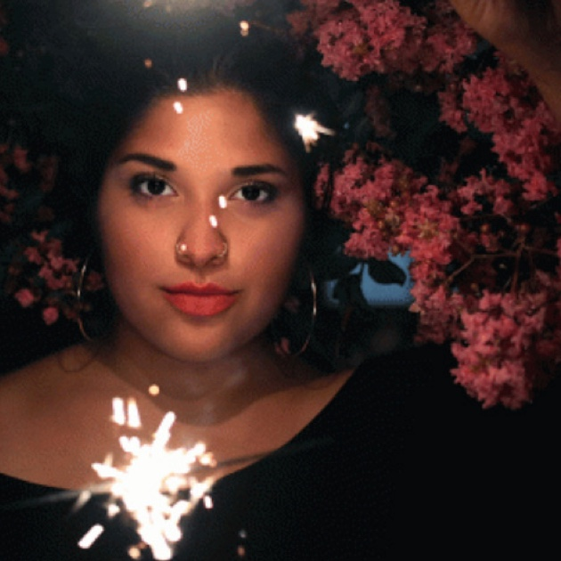 Portrait of a woman with a sparkler and pink trees in the background