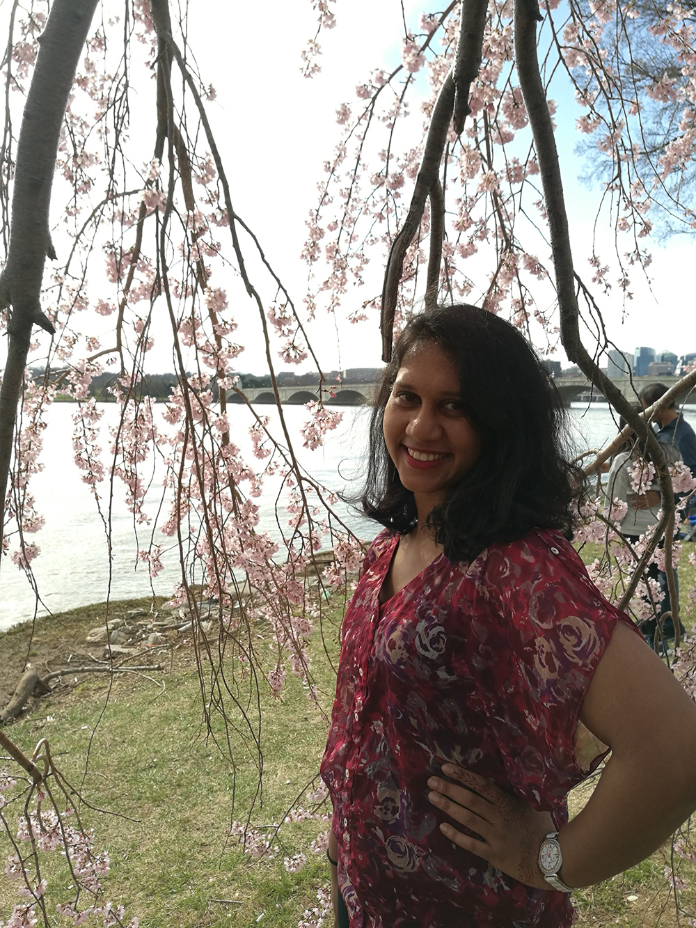 Priya Lewis in front of cherry blossom trees