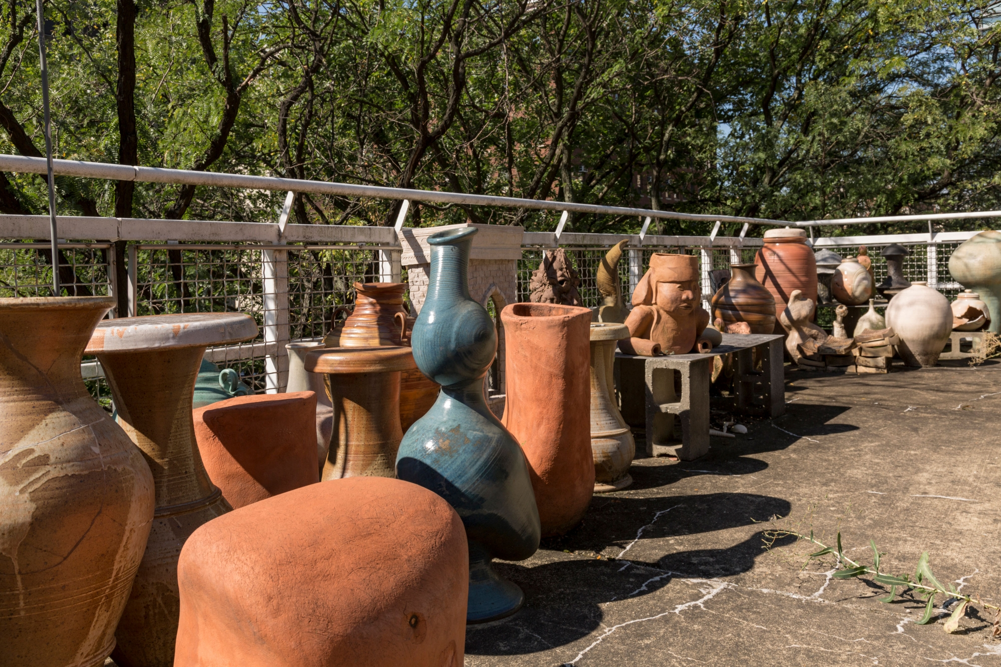 Several rows of large ceramic vases sit alongside a fence