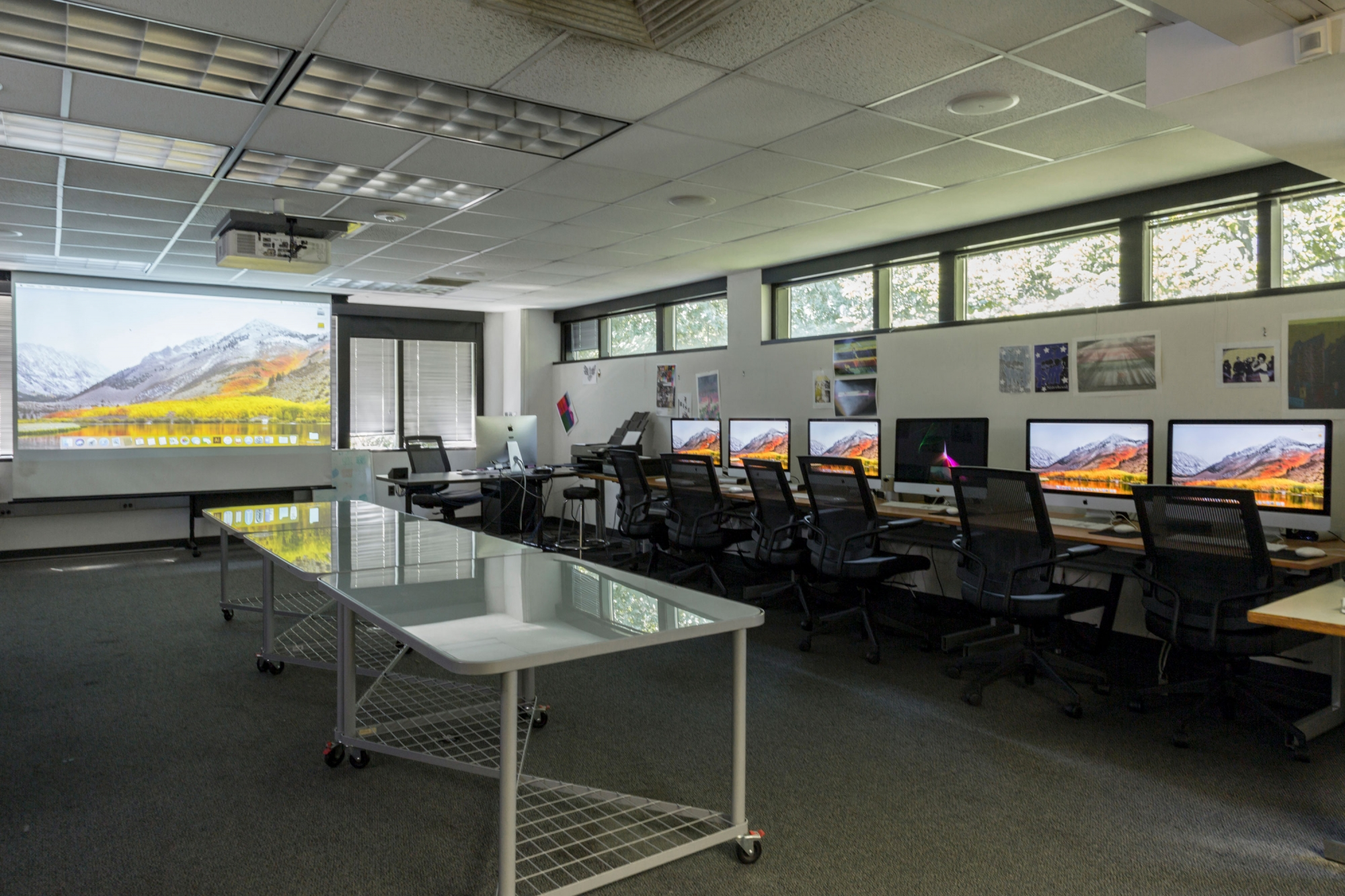 Mac computers sit at stations alongside a window and a several tables on wheels run down the center of the lab
