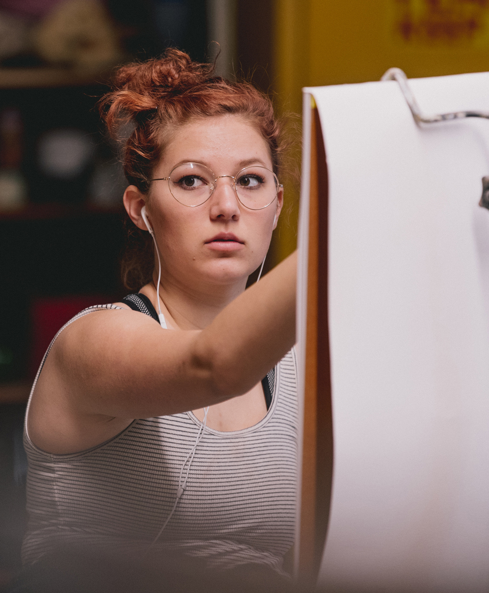 Female student drawing at easel
