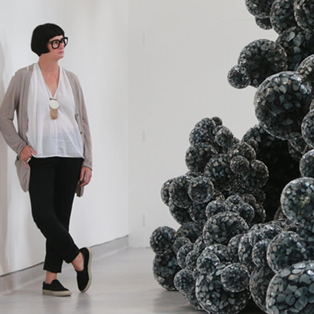 Tara Donovan leaning against wall beside sculpture