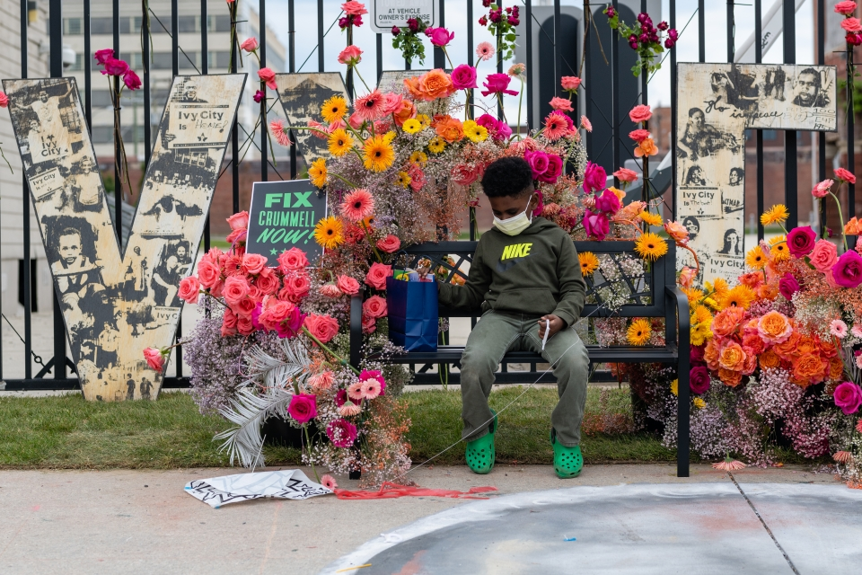 Child sits amongst the flowers in the Floralscapes installation.