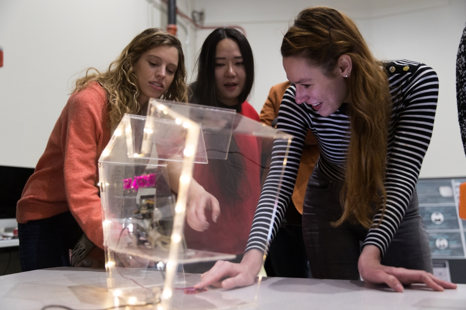 students examining their interaction design project