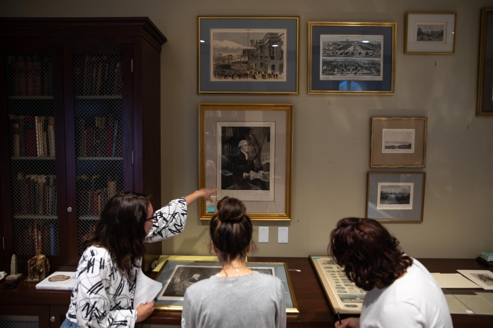 """Students from Denver Brunsman's """"George Washington and His World"""" class examine artifacts from the Albert H. Small Washingtonian"""