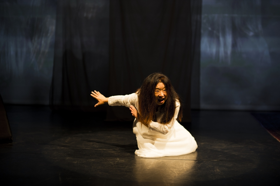 "Hong kneeling while performing in ""On the Threshold of Winter."""