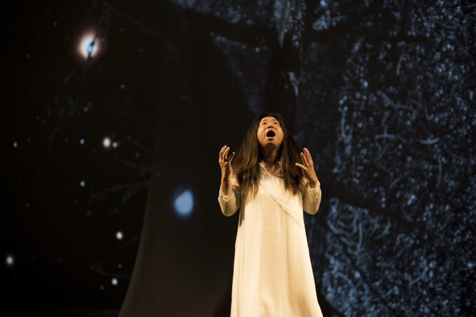 "Hong looks upwards while performing in ""On the Threshold of Winter."""