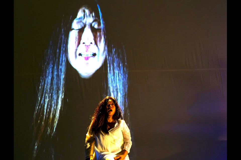 "Hong cries, her face projected onto the backdrop behind her, in ""On the Threshold of Winter."""