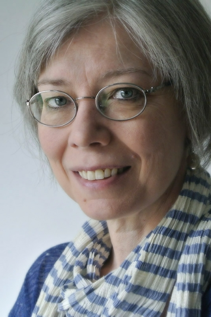 Photograph of woman with glasses checkered scarf.