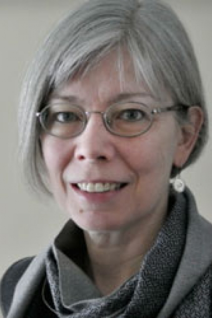 Photograph of woman with glasses and grey scarf.