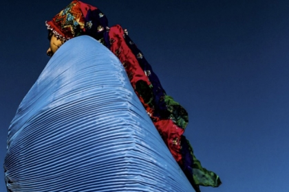 An Afghan woman in elaborate clothing with a blue pleated shawl
