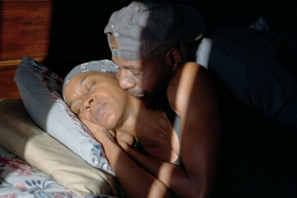 Lashonia and Sean Thompson-El lay in bed together in sunlight.