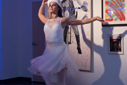 A dancer dressed in white spins in front of a wall covered in visual art.