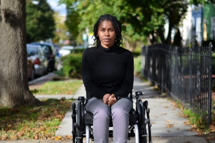 Alumna Tyree Brown sitting in her wheelchair on the sidewalk.