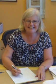 photo of kathy southern seated at a desk writing on a piece of paper
